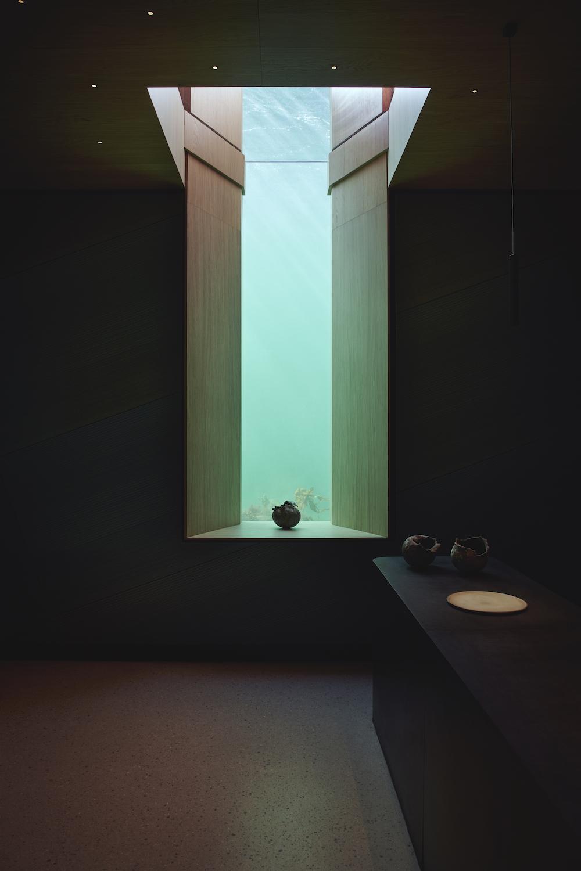 På billedet ses et højt glas vindue, der tillader naturligt lys at strømme ind i rummet og samtidig giver udkig til havet