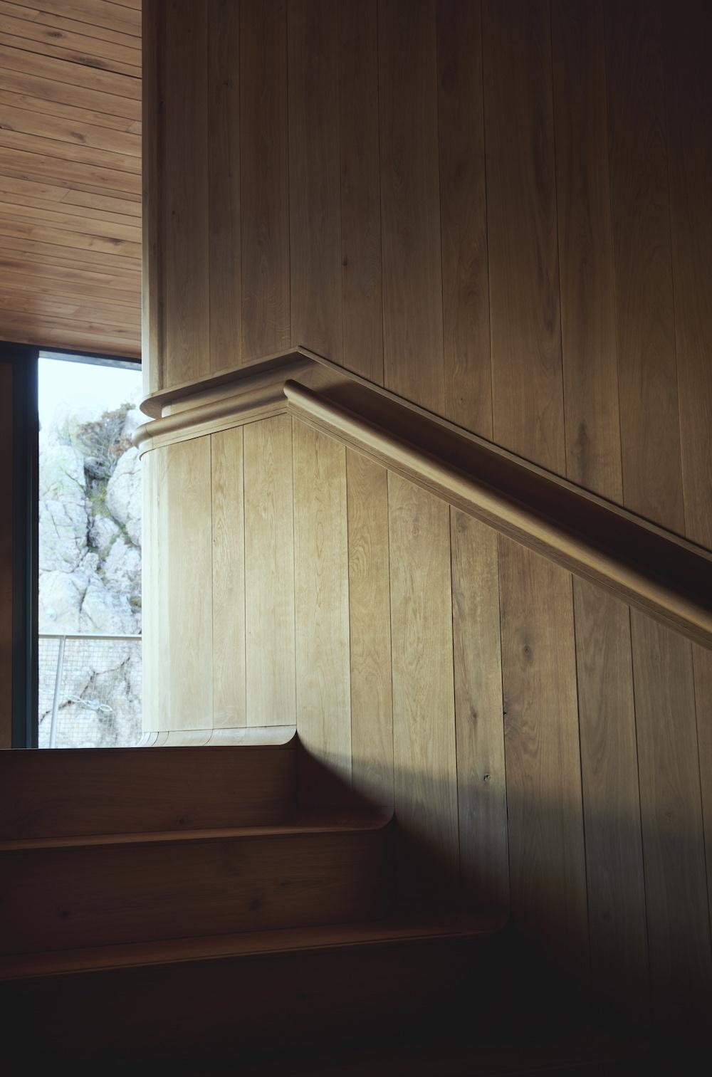 Her ses et billede af trappeopgangen hvor et trægelænder er freset ind i den træbeklædte væg