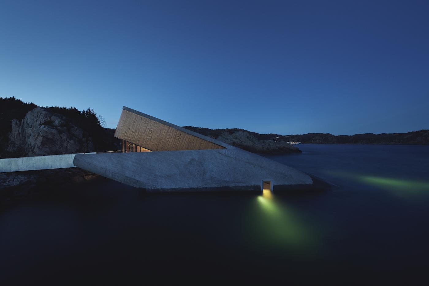 Vi ser restauranten udefra om aftenen og hvordan det særlige udendørs lysdesign giver en hel særlig oplevelse, når det er mørkt. Lyset fra havet får vanden til at ligne en nattehimmel med nordlys.