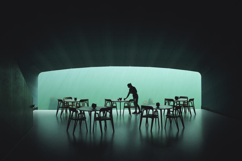 Billede af de fem rundetræborde, der står tættest ud mod der store panoramavindue med havudsigt. En tjener er i gang med at dække bordet på første række.