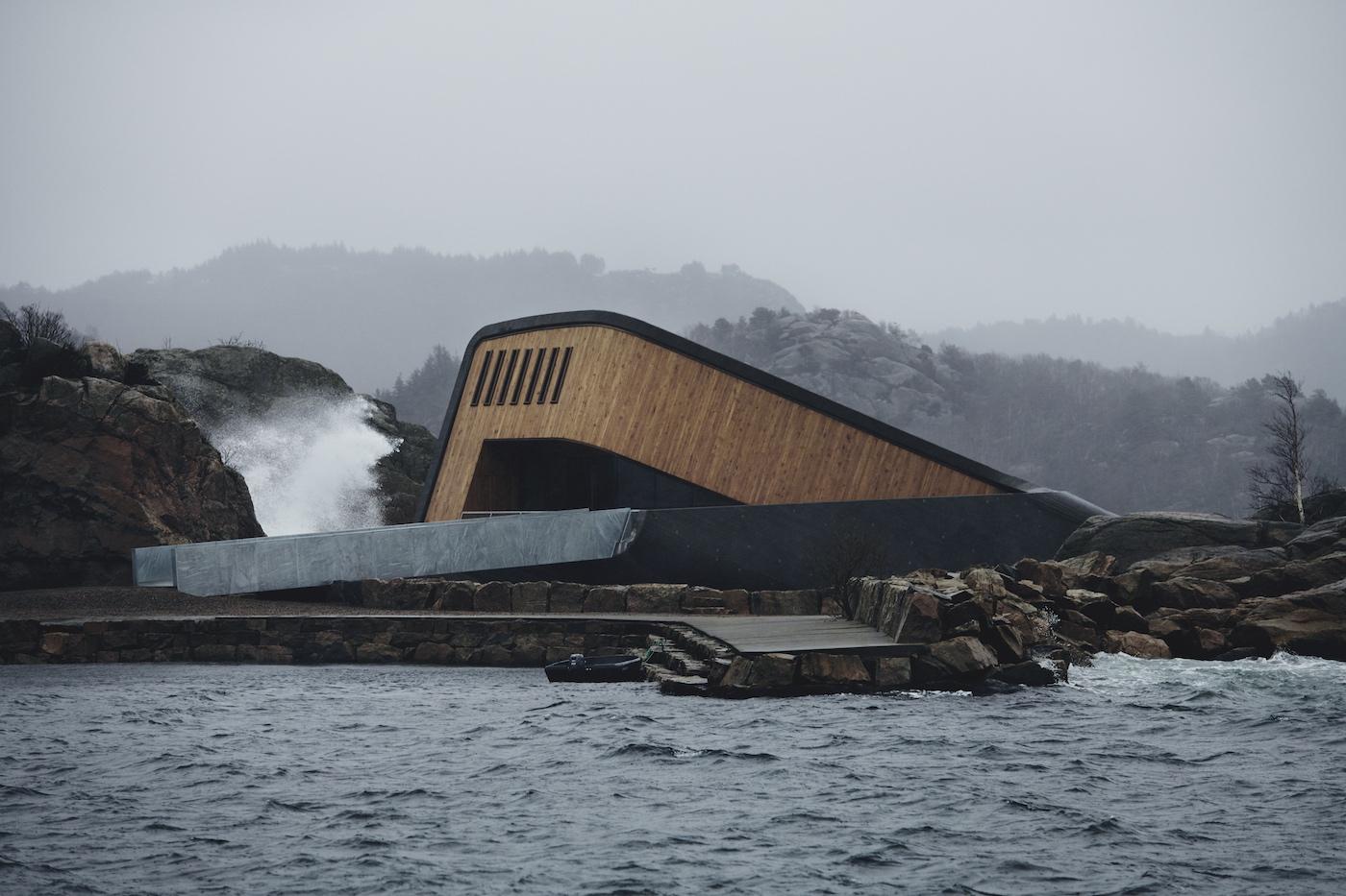 Vi ser her Restaurant Unders placering i det normalt ufrakommelige klippelandskaber. Bølgerne står højt op om den rampe, der leder op til den træklædte restaurant. En anden bred træsti leder direkte ned til havet.