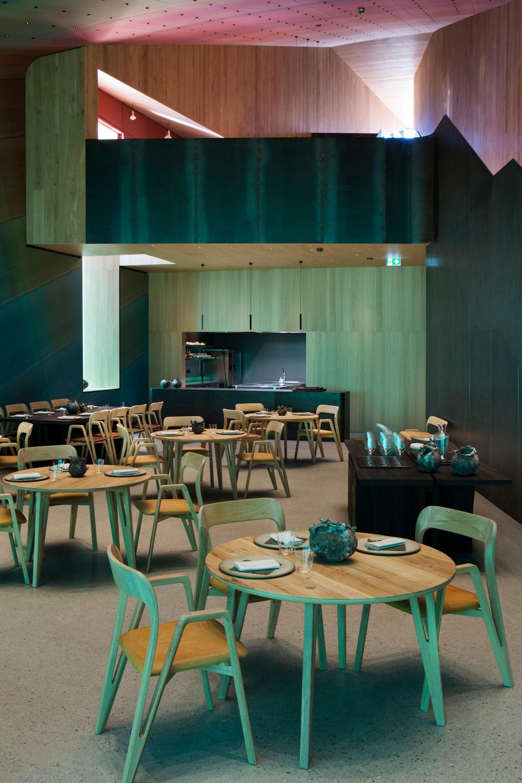På billedet ser vi restaurantens spiseområde med runde træborde og træstole. Bagerst ser vi det åbne blik ud til køkkenet og der er åbnet op, så man kan se op gennem bygningen.