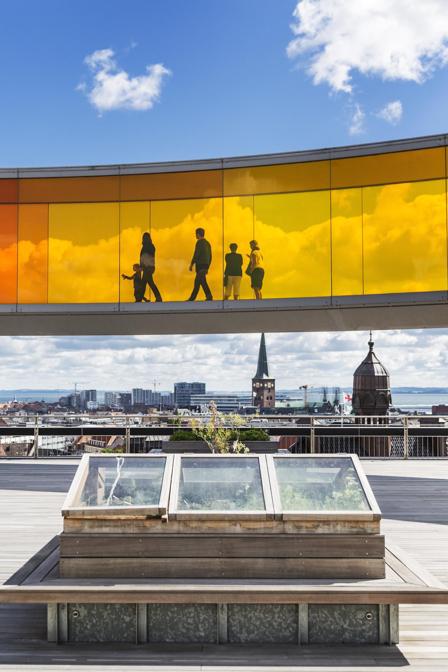 Her ser vi Your Rainbow Panorama øverst, som den bevæger sig henover tagterrassen, som tilbyder en unik udsigt over byen. Der går mennesker rundt i glasgangen og får en kunstoplevelse.