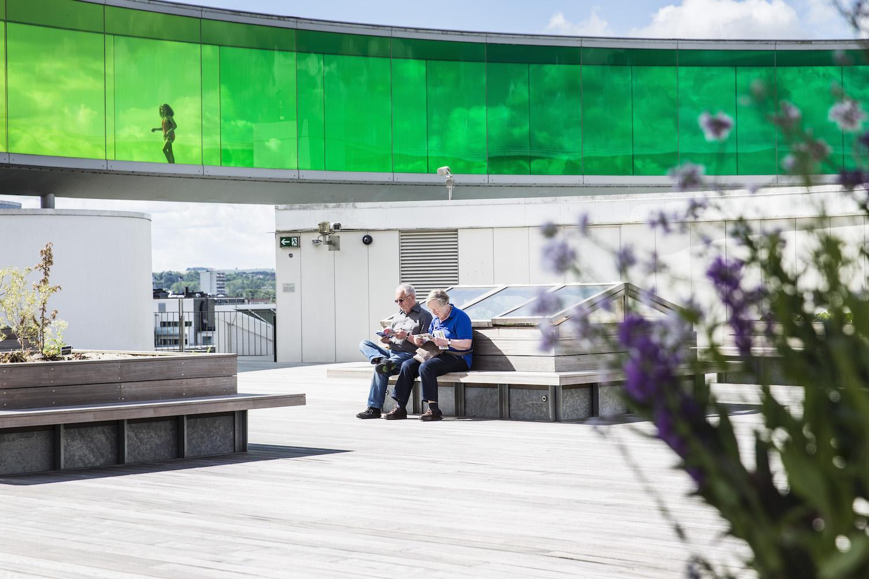 Her ser vi to ældre besøgende på museet, der nyder et roligt øjeblik på en af tagterrassens mange siddemuligheder. Herfra har de samtidig et smukt blik på den farvede glasregnbue.