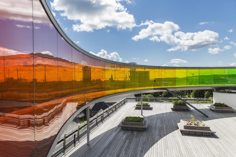 På billedet ser vi Your Rainbow Panorama fra siden med udsigt ud over Aarhus by gennem det farvede glas og med blik udover den store tagterrasse af træ med masser af siddemuligheder.