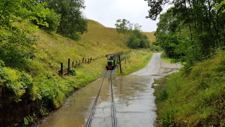 På billedet ses det lille tog, der fører både passagerer, barnevogne og kørestole både hen til og gennem gruberne.