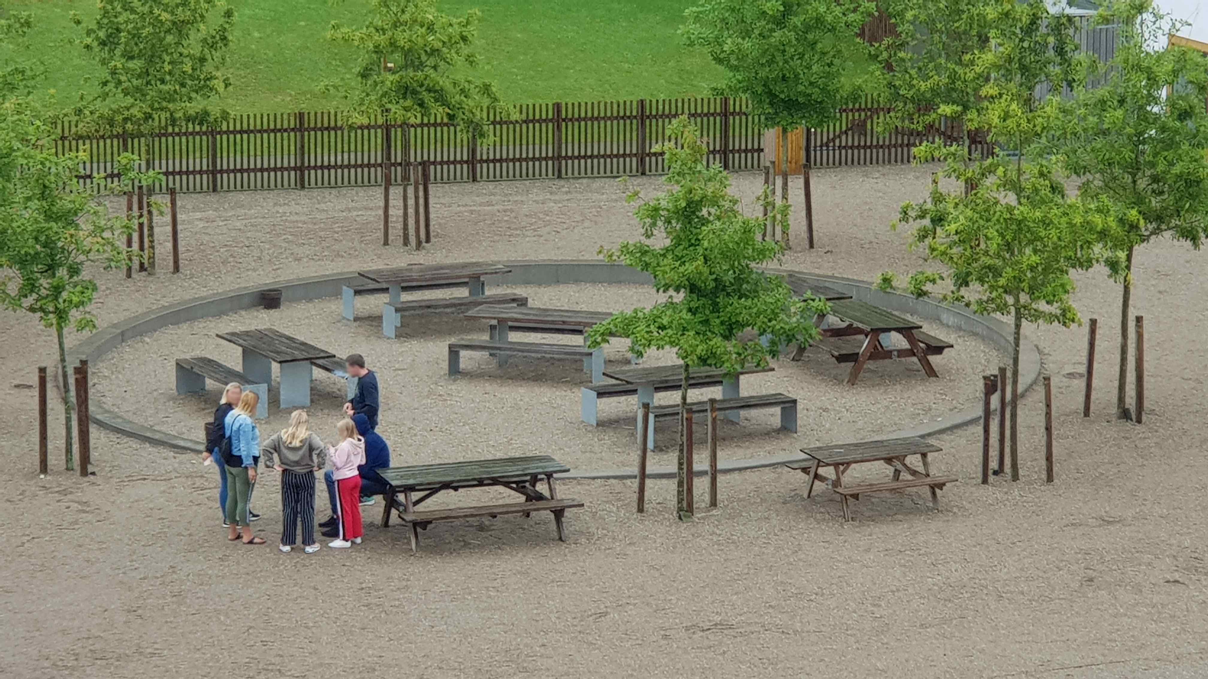 Man kan på billedet se en gruppe mennesker, der er samlet ved området i Mønsted Kalkgrube, hvor der er forskellige bord-bænkesæt.
