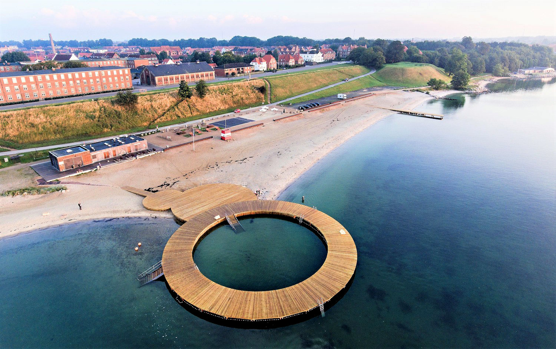 På dette luftfoto ses cirkelbroen der med dirkete forbindelse til standens hovedbygning skaber adgang til både strand og vand