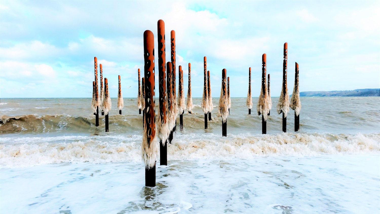 """Et billede af de 28 stålsøjler kaldet """"Havfruefløjterne"""", der er blevet opsat i havet ved Fredericia"""