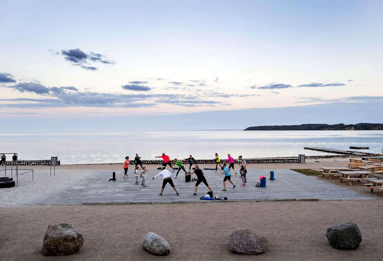 På billedet ses et træbelagt område ved vandet hvor en flok kvinder og børn dyrker morgengymnastik