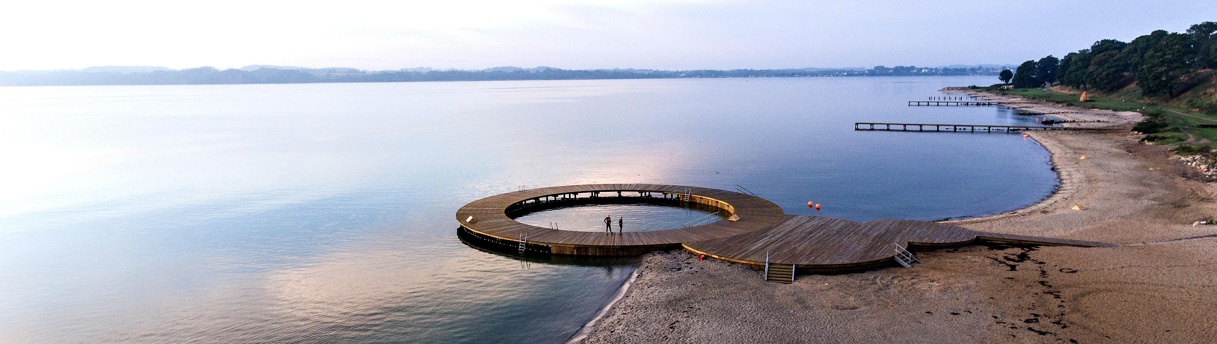 Et billede af kyststrækningen, som viser at den nye cirkelbro blot er én blandt fire nye badebroer langs med stranden.