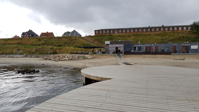 Et billede taget ude fra Cirkelbroen, hvor man kan se en rampe der fører trygt hen til den lille strandcafé