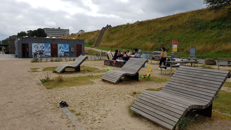 På billedet ses tre store siddemøbler i forgrunden samt en gruppe mennesker der benytter borde-bænkesættet i baggrunden til picnic