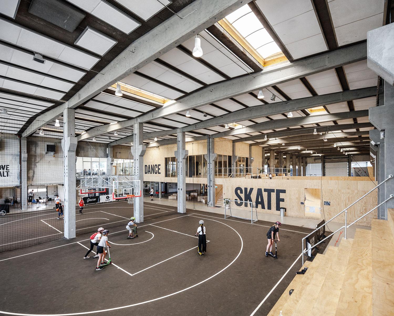 Et billede af den store hal, hvor der er lavet baner til både basket og indendørs fodbold. På billedet ser vi hvordan faciliteterne bruges af mange forskellige børn og unge, i forskellige aldre og muligheder.