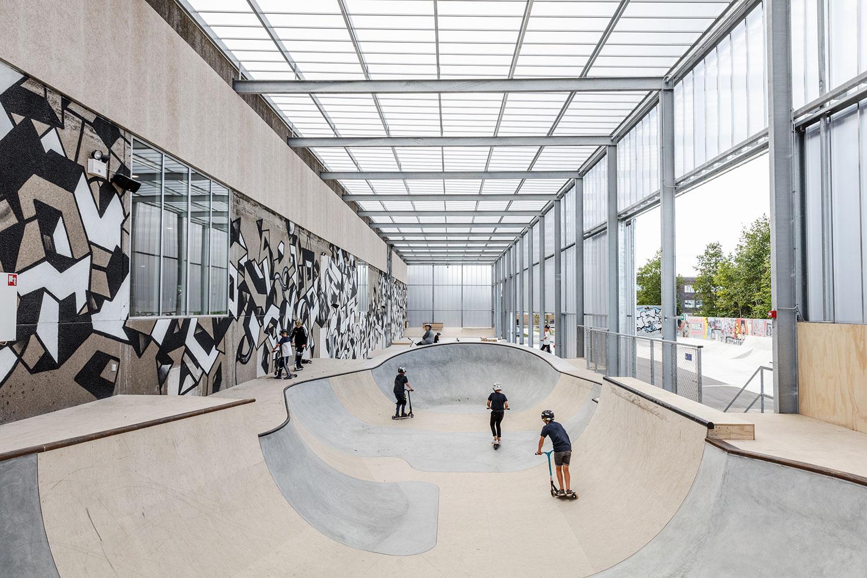 Et blik indi den halvåbne skatehal, der bliver brugt af unge drenge på deres skateboards. Hallen er lavet med lyst plastik, så rummet føles åbent og lyst.