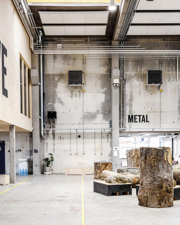 På billedet ses store træstubbe, der med deres placering midt i den transformerede rå fabriksbygning inviterer til alternative aktiviteter