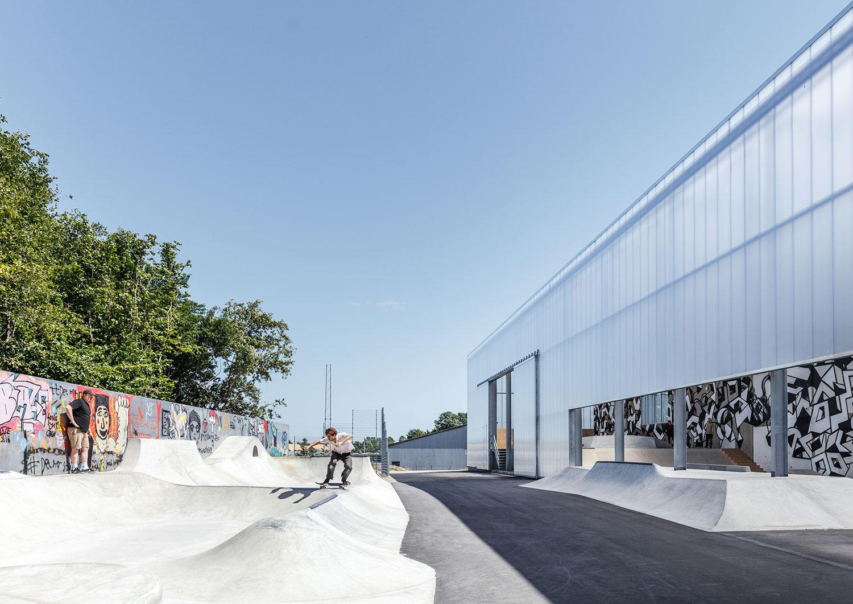 Vi ser de udendørs skateramper og den halvåbne facade ind til de øvrige skatefaciliteter, der også kan benyttes uden for åbningstid. På billedet ser vi en voksen mand og en dreng, der bruger skateramperne.