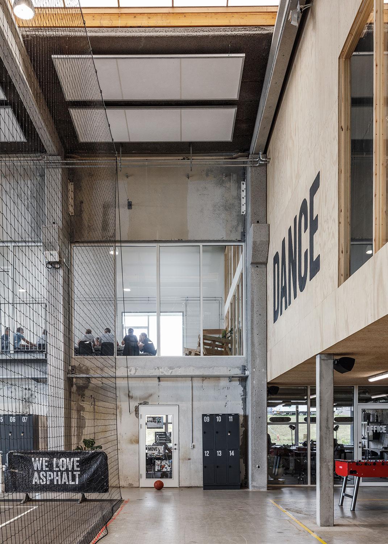 Billedet illustrerer, hvordan der er arbejdet med forskellige niveauer og planer i den åbne bygning, hvor naturlige træpaneler går i dialog med de industrielle betonoverflader.