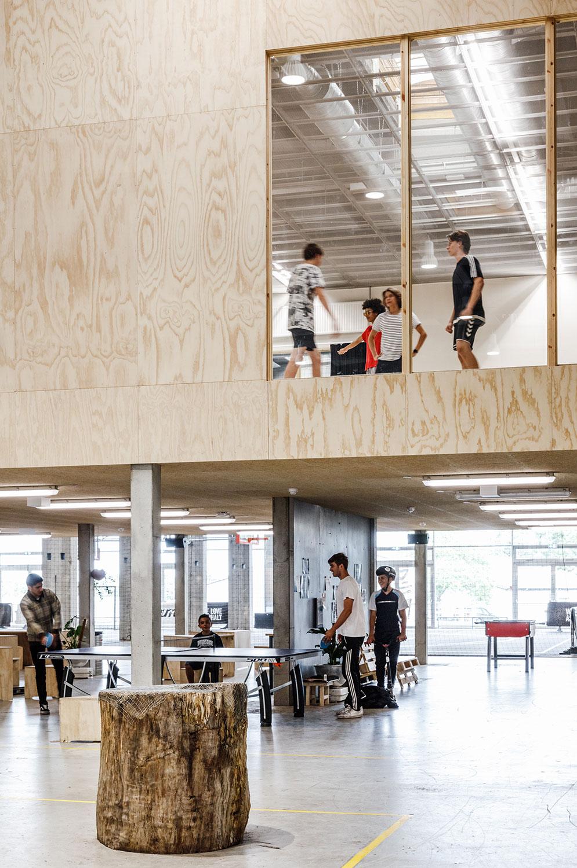 Billedet viser den åbne forbindelse mellem etager, hvor man kan følge med i rummenes aktiviteter: I stuen spiller en flok bordtennis og på første sal er der danseundervisning.