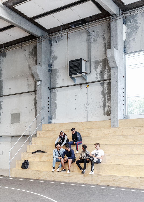 BIlledet viser den trætribune, der er opstillet ved sportsbanerne. Vi ser en gruppe unge, der snakker med hinanden og måske knytter nye venskaber – det der foregår uden for sporten er også indtænkt i GAME.