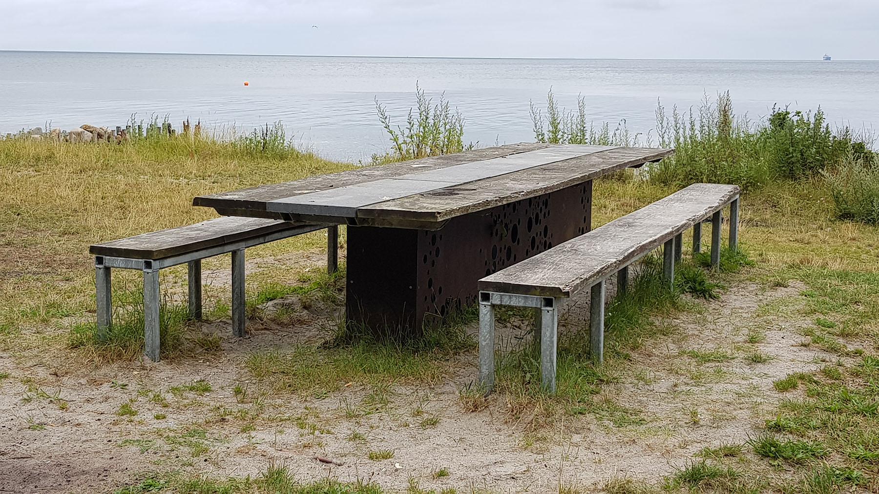 På billedet ses et langbord med tilhørende bænke, der er placeret i et grønt område tæt på vandet