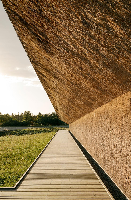 Der er brugt tækkede facader, som går i dialog med tagets skrå linjer. Vi ser gangbroen af træ, som leder rundt om centret og enten indenfor eller ud i naturen.
