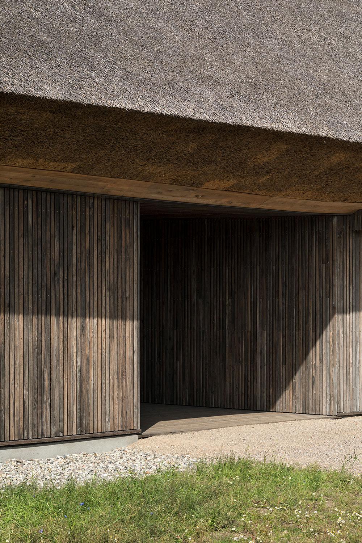 På billedet ses det tykke stråtag, der danner skygger på den træbelagte facade og desuden skaber et naturligt udtryk