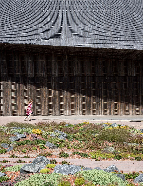 Vi ser Vadehavscentret udefra og tætpå og hvordan træfacaden og det moderne stråtag går i forbindelse med den naturlige tundragård. Vi ser også en lille pige løbe langs facaden.