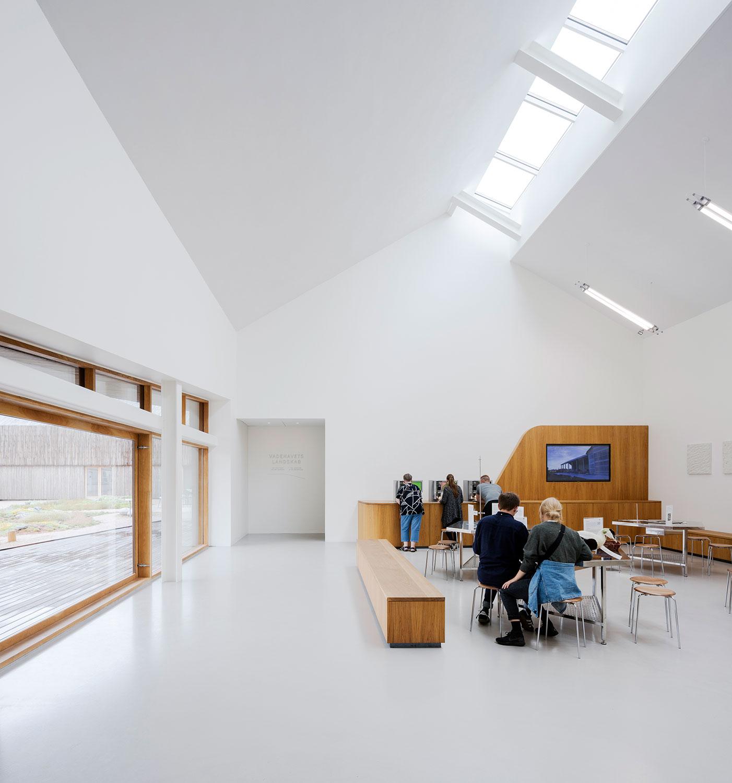 Billedet viser et stort opholdsrum, hvor der er forskellige siddemuligheder og ekstraordinære lysforhold fra de store ovenlysvinduer og det store vinduesparti.