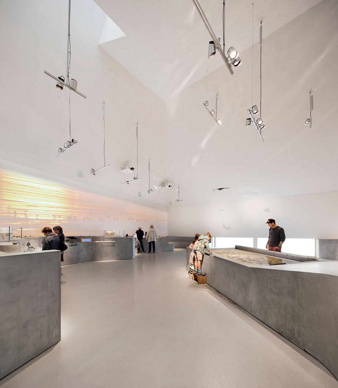 Billedet viser, hvordan besøgende interagerer med udstillingen på forskellige måder og i forskellige højder, så både voksne og børn kan være med.