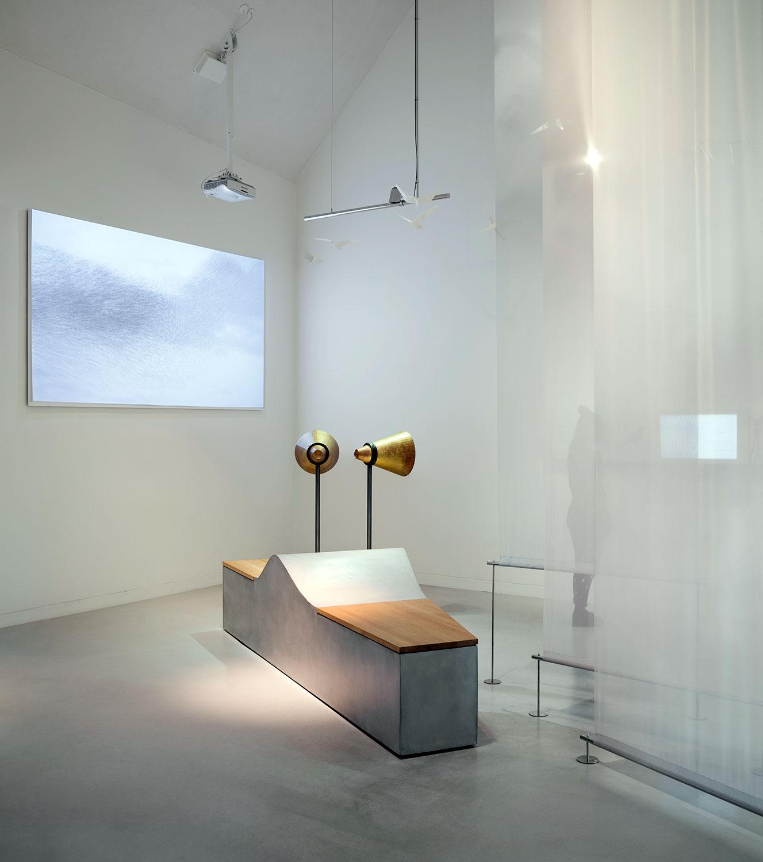 Et billede af en centralt placeret bænk, hvorpå man kan sidde mens man betragter udstillingen fra forskellige vinkler. Her kan alle deltage.