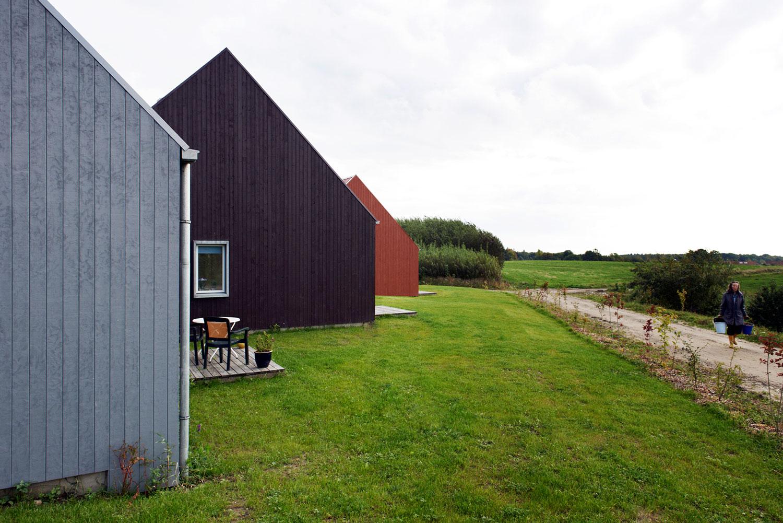 Et skråbillede af tre boliger, hvor man aner, at hver bolig har sin egen lille terrasse med udsyn mod naturen, den lille sø og grusstien, der forbinder samfundet.
