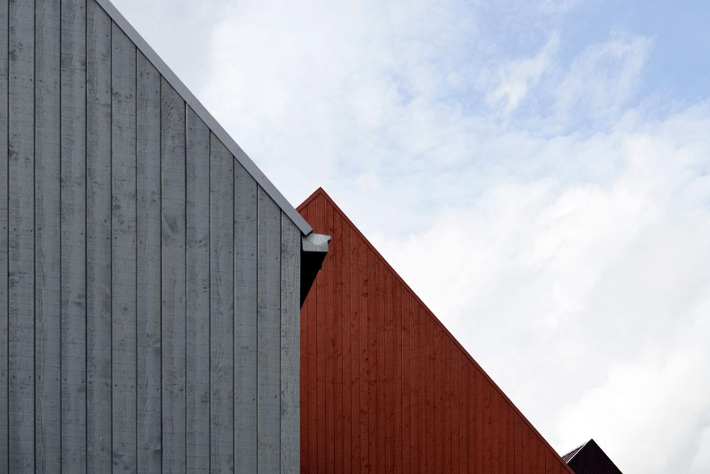 Et nærbillede der viser de skrå, træbeklædte facader. De farverige huse gør det nemt at navigere i Anddelssamfundet i Hjortshøj og bidrager desuden til sanselighed.