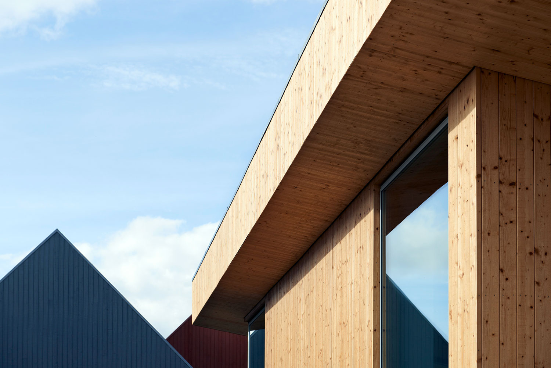 Et nærbillede af boligerne i Bogruppe 6, der er beklædt med træ, der enten fremstår naturligt eller malet. Billedet viser også et stort vindue, som medskaber de gode lysforhold til boligerne.