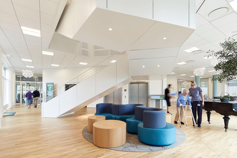 Stort hvidt lokale i Akaciegården. Trappe går op til næste sal. Blå sofa og to sofaborde står i midten af lokalet. Der står et flygel til højre. Kvinde går med gangstativ og bliver hjulpet af ansat