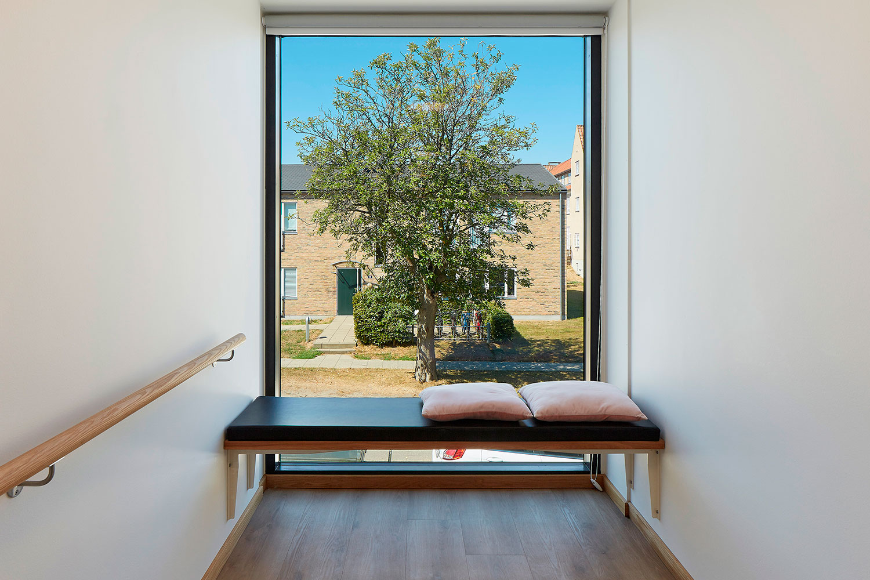 Rum med vindue fra gulv til luft med bænk foran. Udsigt til træ og bygning