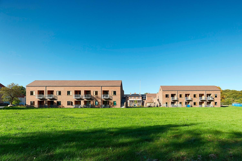 Bygningerne er omringet af grønne omgivelser i form af græsplæne, træer osv.