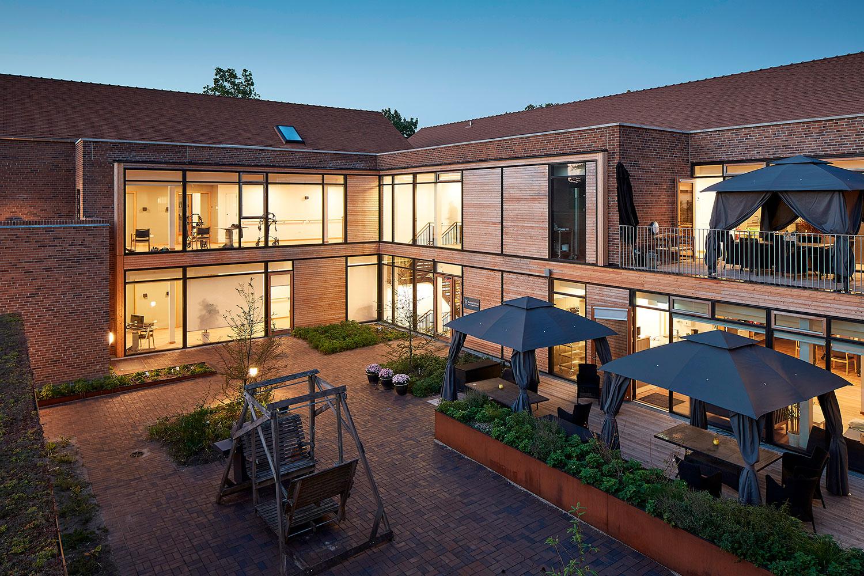 Der er mange glaspartier i bygningen. De skaber en visuel forbindelse mellem gårdrum og fællesrum inde i bygningen.