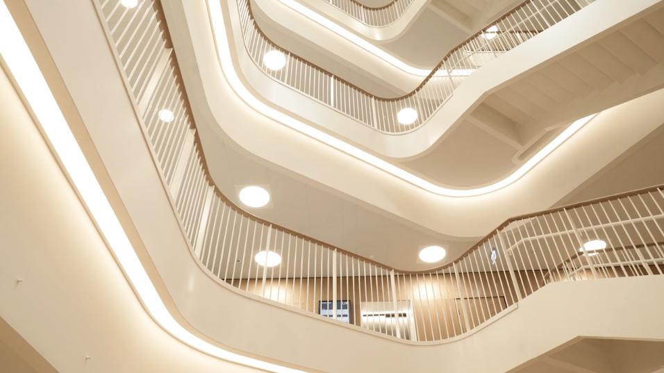 Hvid bygning indenvendigt med kig op til forskellige bølgende etager og trapper