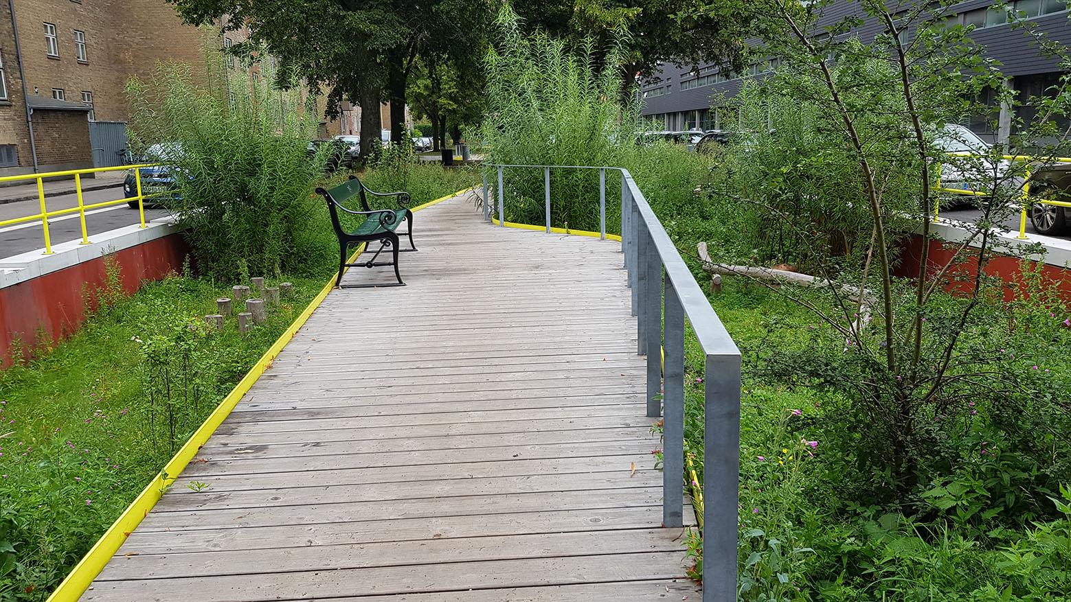 Kanterne til gangbroerne er designet i farverigt materiale, der fanger øjet. Selve broen er bygget i træ.