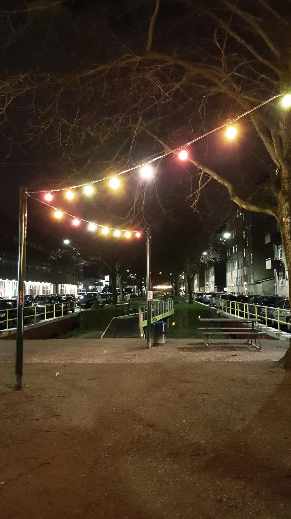 Scandiagade om natten med kulørte lysende lamper.