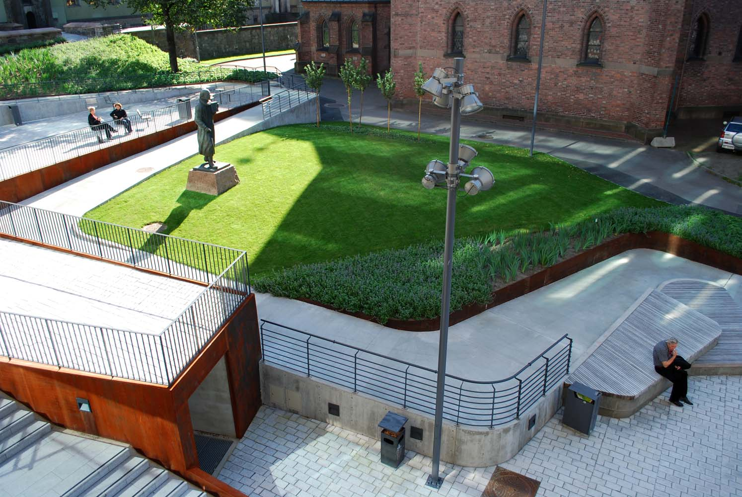 Pladsens grønne, kobber- og betonfarver er valgt til at matche omgivelserne.