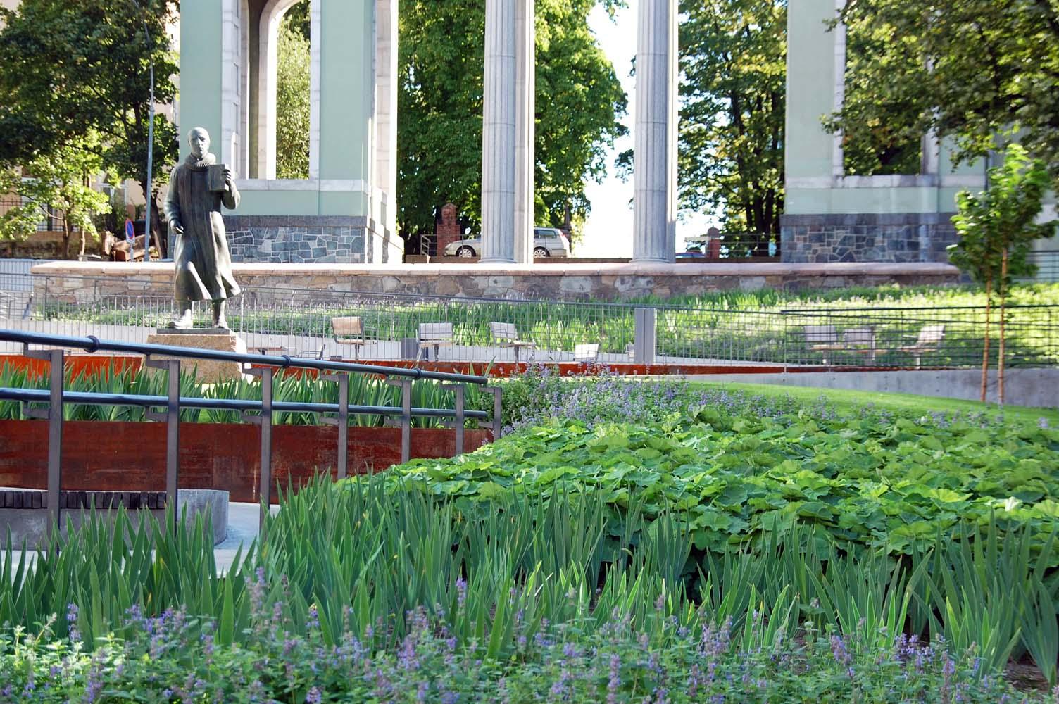 En statue midt på pladsen er omringet af grønne planter.