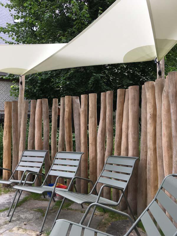 Træpæle med mellemrum der giver udsigt til resten af haven.