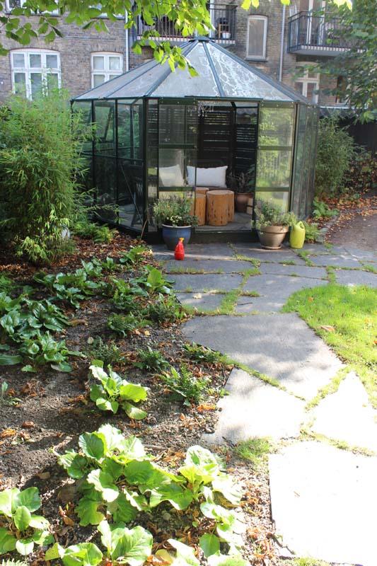 En pavillon som er tilbagetrukket fra resten af haven.