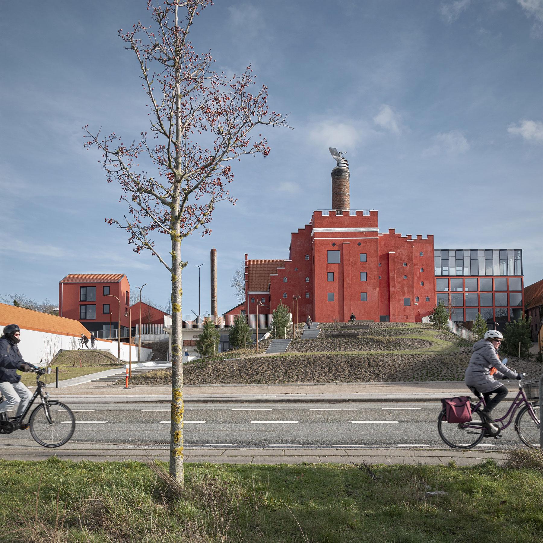 Den røde bygning Maltfabrikken i baggrunden og en vej og to cyklister i forgrunden
