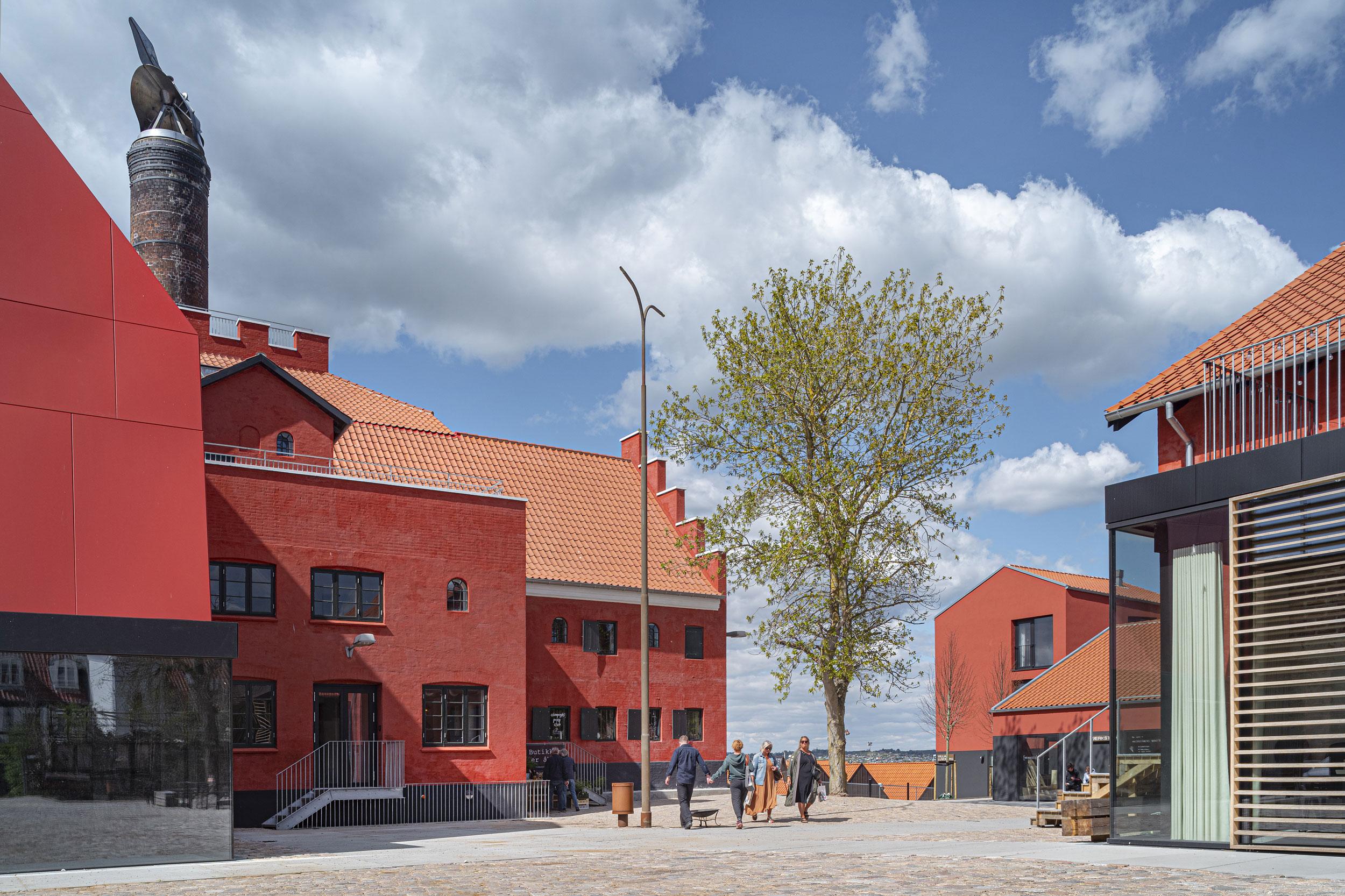 Gårdsplads med røde bygninger og et træ