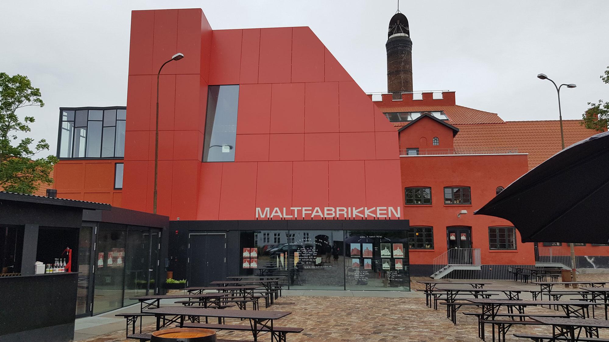 Borde og bænke i forgrunden og røde bygninger i baggrunden, den ene med et skilt på taget, hvorpå der står Maltfabrikken
