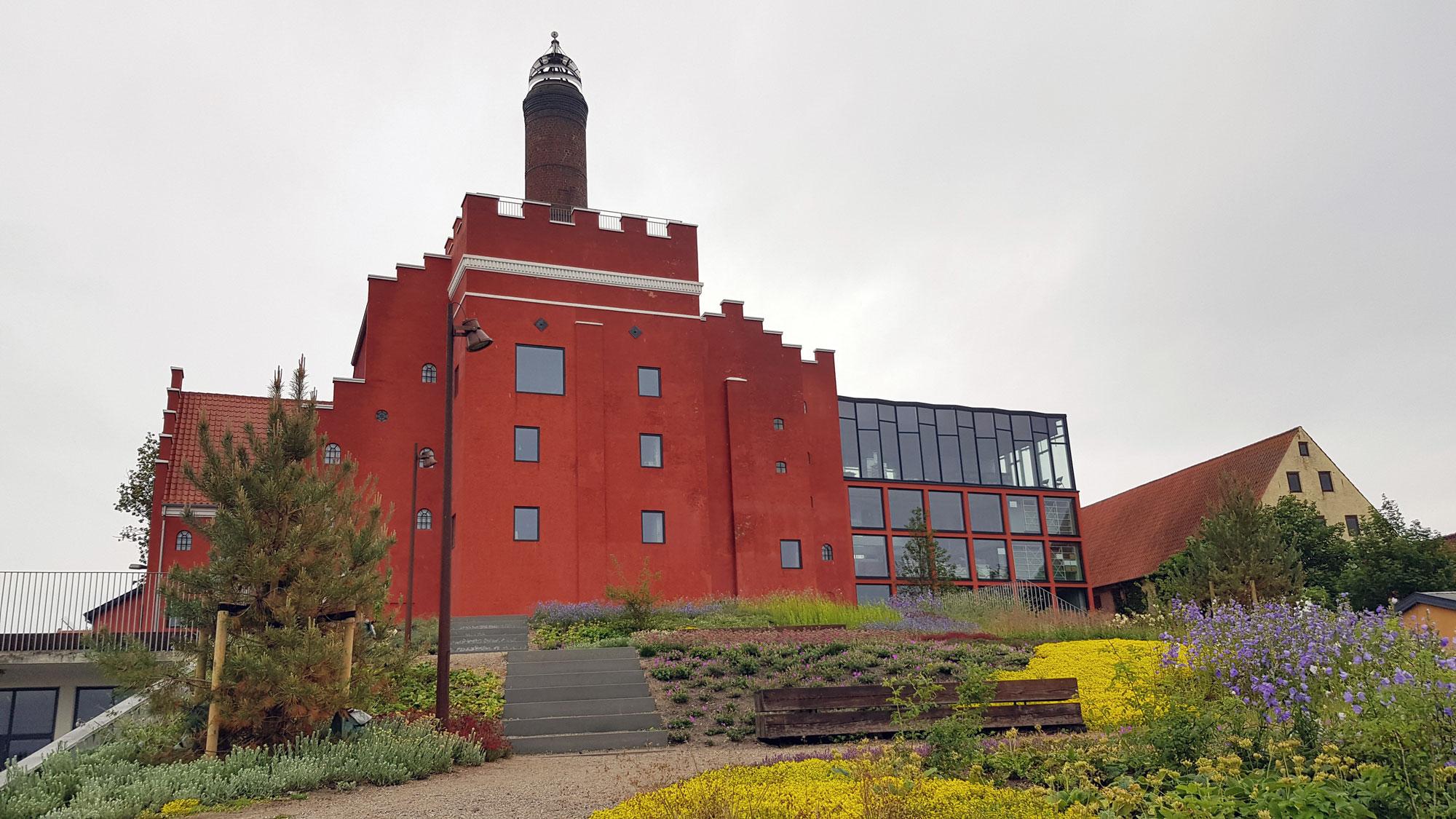 Den røde bygning Maltfabrikken med bevoksning og blomster foran
