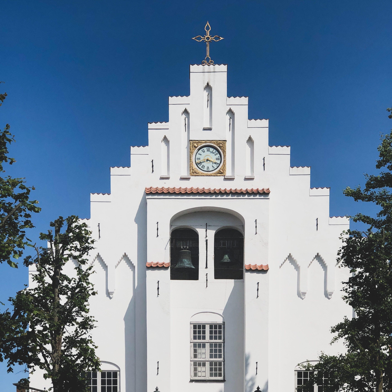 Toppen af hvid kirke med to klokker, kirkeur og et kors på toppen